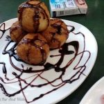 Yucca balls filled with cheese and drizzled with chocolate sauce.